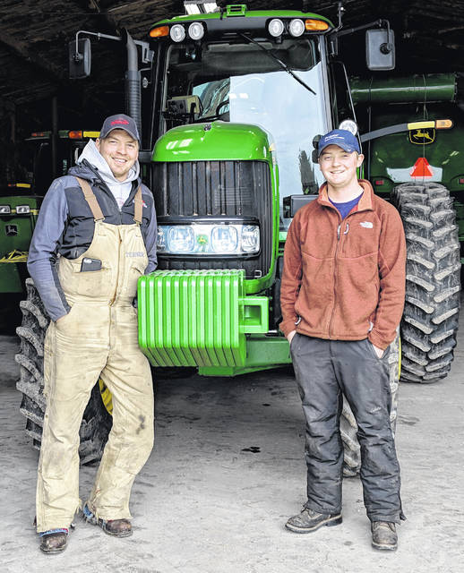 Lee Turner, left, and his brother, Brandon Turner, pose with farm equipment on their recently-purchased farm, Scioto Prairie Farms in Auglaize County.