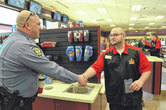 Ottawa Police Officer Shane Vance introduces himself to Casey's store manager Dann Wiler while the officer the variety of new coffee options during the soft opening of the new convience store.