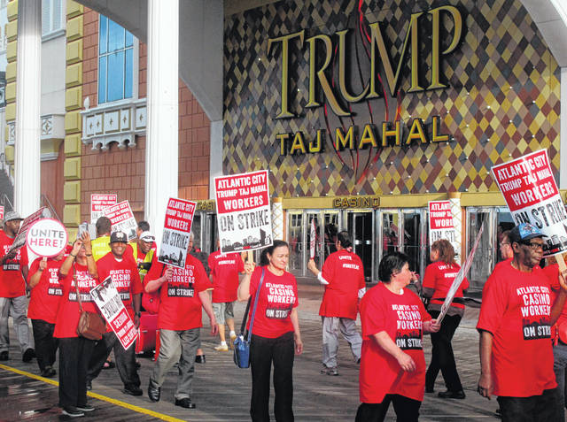 In this July 1, 2016, photo, members of Local 54 of the Unite Here casino workers union picket outside the Trump Taj Mahal casino in Atlantic City N.J. shortly after going on strike against the casino, which was owned by billionaire investor Carl Icahn. On Wednesday, April 10, 2019, the union called on casino regulators in New Jersey, Nevada and Ohio to protect casino workers from hedge fund or private equity firms that own casinos if they seek to quickly extract profits from the properties while hurting workers.