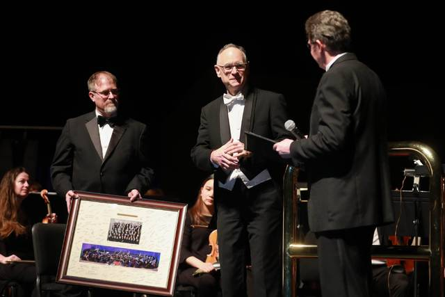 Conductor Mark Suderman (right) and Concert Master Michael Houff present a framed photograph to Maestro Crafton Beck of the Lima Symphony Orchestra at his last concert on Saturday evening. Amanda Wilson -The Lima News