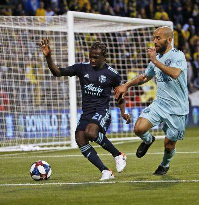 Portland's Diego Chara (21) tries to keep the ball against the Crew's Federico Higuain during Saturday night's game in Columbus.