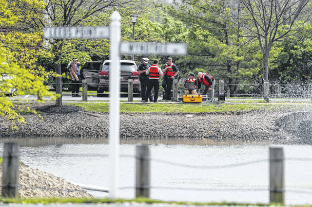 Police authorities search a nearby pond at a scene at an apartment complex Monday, April 29, 2019, in West Chester, Ohio. Several people were found dead at the apartment complex where multiple gunshots were fired, police said Monday. No suspect has been identified.