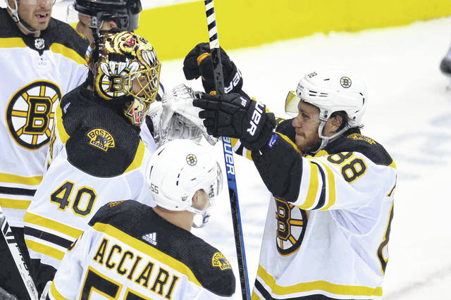 Boston Bruins right wing David Pastrnak (88) celebrates with goaltender Tuukka Rask (40) and center Noel Acciari (55) after defeating the Toronto Maple Leafs in Game 6 of an NHL hockey first-round playoff series Sunday, April 21, 2019, in Toronto. (Frank Gunn/The Canadian Press via AP)