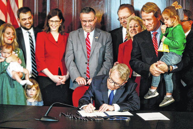 Gov. Mike DeWine speaks before signing a bill imposing one of the nation's toughest abortion restrictions, Thursday, April 11, 2019 in Columbus, Ohio. Lt. Governor Jon A. Husted stands at right holding Faye Zaffini, 2, the daughter of his chief of staff. DeWine's signature makes Ohio the fifth state to ban abortions after the first detectable fetal heartbeat. That can come as early as five or six weeks into pregnancy, before many women know they're pregnant.