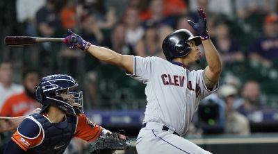 Cleveland Indians' Francisco Lindor, right, hits a two-run home run as Astros catcher Robinson Chirinos watches during the ninth inning of Friday night's game in Houston. (AP photo)