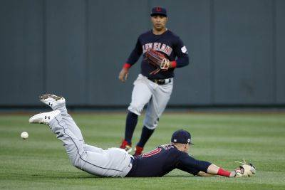 Cleveland Indians center fielder Leonys Martin, top, looks on as left fielder Jake Bauers, bottom, is unable to catch a short fly ball by Kansas City Royals batter Hunter Dozier during the first inning of Friday night's game at Kauffman Stadium in Kansas City, Mo. (AP photo)