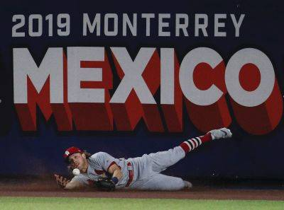 St. Louis Cardinals' Harrison Bader can't make the catch, resulgint in a triple by Cincinnati's Phillip Ervin during the eighth inning of Saturday night's game in Monterrey, Mexico. (AP photo)
