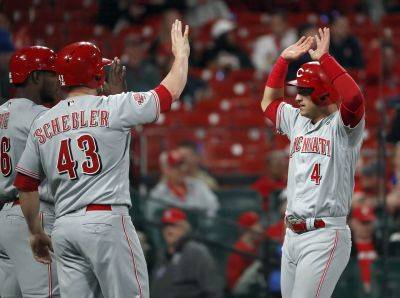 Cincinnati's Jose Iglesias (4) celebrates with teammates Scott Schebler (43) and Yasiel Puig after scoring on a three-run double by Curt Casali during the ninth inning of Friday night's game against the Cardinals in St. Louis. (AP photo)
