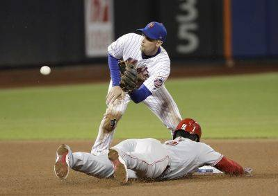Cincinnati's Yasiel Puig reaches second base safely to record a stolen base against the Mets Jeff McNeil during Tuesday night's game in New York. (AP photo)