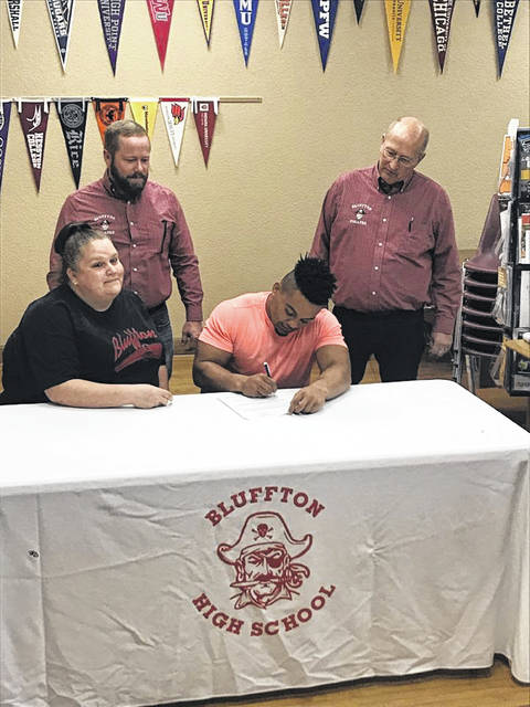 Bluffton's DeAndre Nassar is joined by his mom, Amber Brodman, and, from left, Bluffton assistant wrestling coach Mike Wilson and Bluffton head wrestling Jeff Kleman as he signs his national letter of intent to wrestle at Cleveland State at the high school Thursday.