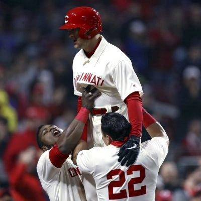 Yasiel Puig, left, and Derek Dietrich, right, hoist Reds teammate Nick Senzel after Senzel hit his first home run in the majors, during the fifth inning of Saturday night's game against tSan Francisco in Cincinnati. (AP photo)