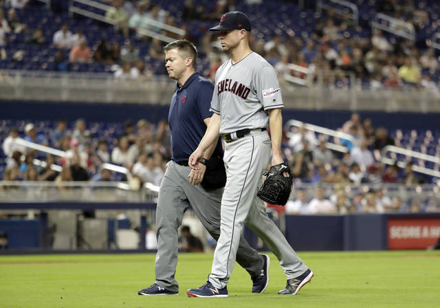 Cleveland Indians starting pitcher Corey Kluber, right, leaves during the fifth inning of the team's baseball game against the Miami Marlins, Wednesday in Miami. Kluber was hit by a single hit by Marlins' Brian Anderson.