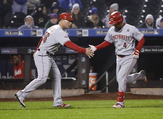 Cincinnati Reds' Jose Iglesias, right, celebrates with third base coach J.R. House after hitting a home run during the ninth inning of the team's baseball game against the New York Mets on Wednesday in New York. The Reds won 1-0.