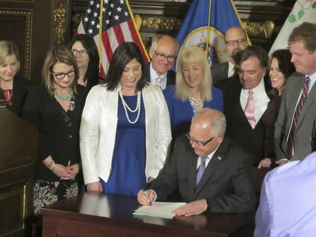 Jenny Teeson, center in white, of Andover, Minnesota, looks on as Minnesota Gov. Tim Walz signs a bill at the Capitol in St. Paul, on Thursday, repealing a Minnesota law that prevented prosecutors from filing sexual assault charges against people accused of raping their spouse. Teeson, testified before legislative committees earlier this year about how her now ex-husband drugged her and made a video of himself raping her while she was unconscious. Prosecutors dropped rape charges because of the old law, and he served just 30 days in jail for invasion of privacy.