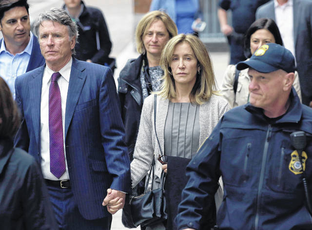 Felicity Huffman, center, departs federal court with her brother Moore Huffman Jr., left, Monday in Boston, where she pleaded guilty to charges in a nationwide college admissions bribery scandal.