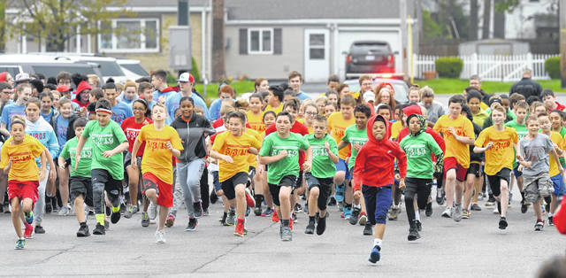 Runners compete in a 5K run during Friday's 35th annual Positive Addiction Week at St. Charles Catholic School.