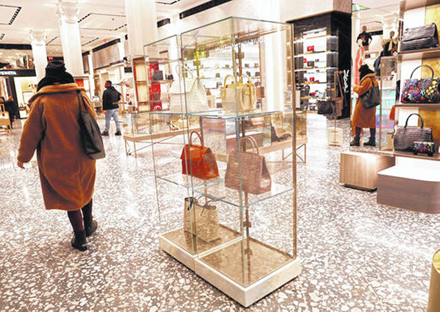 Saks Fifth Avenue shoppers pass through the luxury handbag section Feb. 20 at Saks' flagship store in New York. Shopping can be a form of relaxation, an entertaining way to spend time or even a hobby. But it can turn into an expensive habit.
