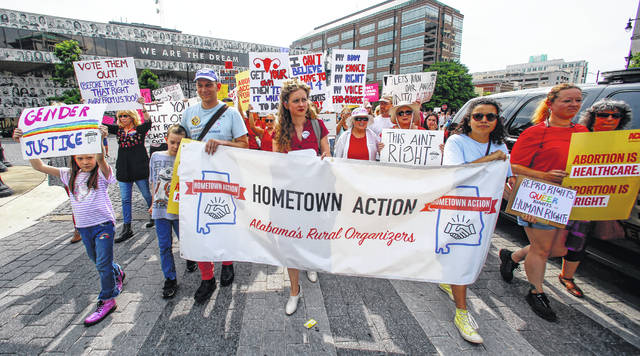 In this May 19, 2019, photo, protesters for women's rights march to the Alabama Capitol to protest a law passed last week making abortion a felony in nearly all cases with no exceptions for cases of rape or incest in Montgomery, Ala. Members of both parties say a flood of laws banning abortions in Republican-run states has handed Democrats a daunting weapon for next year's elections. They say the restrictions will help Democrats paint the GOP as extreme and woo centrist voters who could decide tight House and Senate races.