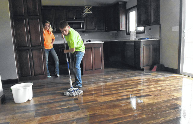 Tyler Lewis, 18, of Apollo's carpentry class mops the kitchen of Apollo Career Center's student built home at 1809 Applejack Drive in Wapakoneta. On the left is Kati Askins, assistant instructor at Apollo. Craig J. Orosz | The Lima News