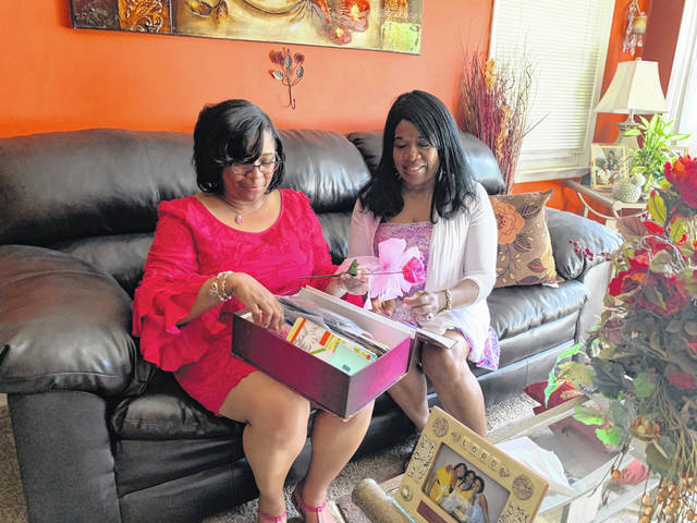 "Ericka Boddie (left) and her mother, Patricia Carter, go through Boddie's ""Hope box,"" which holds all of her hospital bracelets, cards of encouragement and any other mementos from her journey with breast cancer thus far. Written on the box is ""With God, all things are possible."""