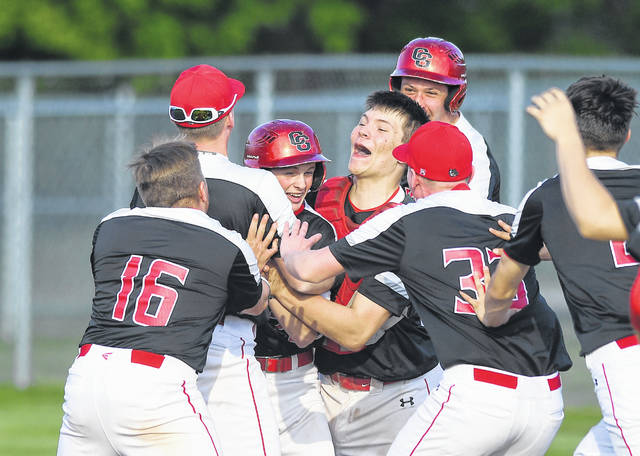 Columbus Grove teammates rush Luke Otto after he knocked in pinch runner Grant McCauley with the winning run in Tuesday night's home Putnam County League game against Kalida.