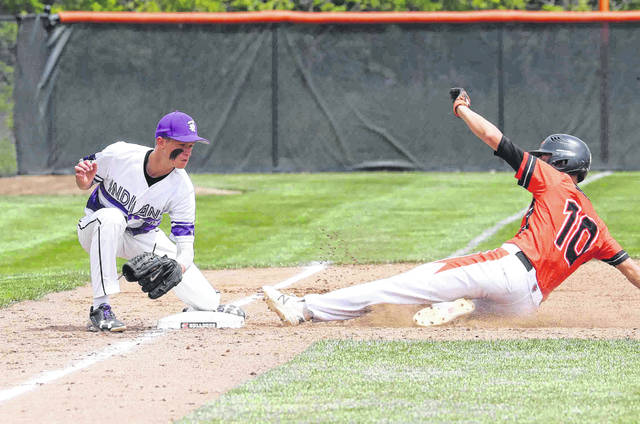 Coldwater's Jacob Wenning slides safely into third base against Fort Recovery's Brock Dues during a Thursday Division III district semifinal at Ed Sandy Field in Elida.