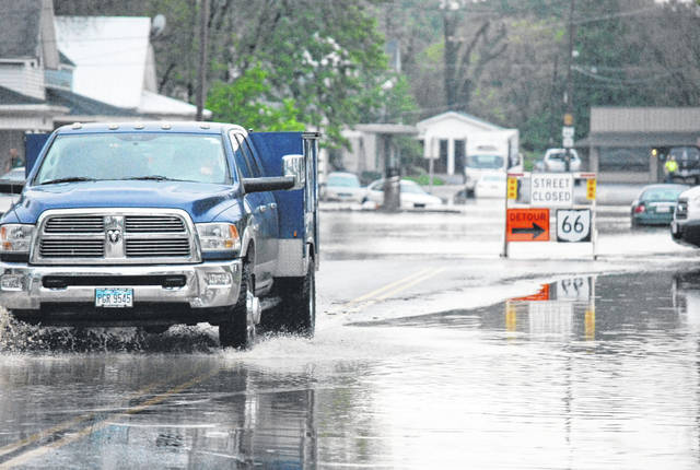 A sign detours people around a flooded roadway Friday morning on state Route 66 in Delphos.