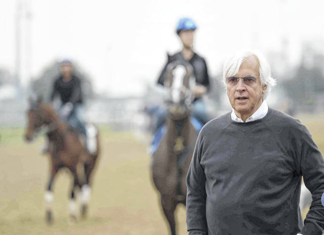 Trainer Bob Baffert, who has three Kentucky Derby hopefuls, watches on the track during a workout at Churchill Downs Tuesday, April 30, 2019, in Louisville, Ky. The 145th running of the Kentucky Derby is scheduled for Saturday, May 4. (AP Photo/Charlie Riedel)