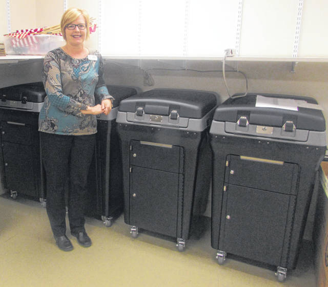 Karen Lammers, Putnam County Board of Elections director, stands next to new voting equipment that was purchased for the county.