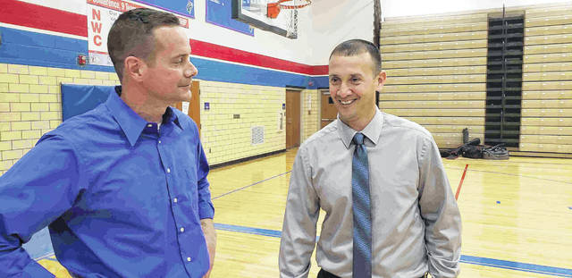 Jeremy Best, who stepped down in late April as Crestview's head boys basketball coach, talks with newly hired head coach Doug Etzler, right, after the Crestview graduate was named the new Knights' coach.