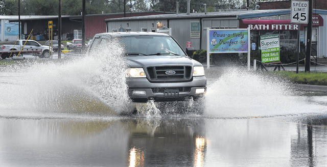 A motorist driving a pickup truck drives through high flood water on state Route 309 early Friday morning after the previous night's torrential downpour caused area flooding.