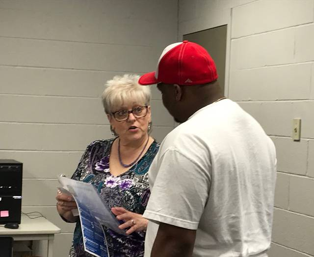 Deb Lowry, a human resources manager with General Dynamics Land Systems, talks with prospective job candidates during an application event for the Joint Systems Manufacturing Center. Mackenzi Klemann | Lima News