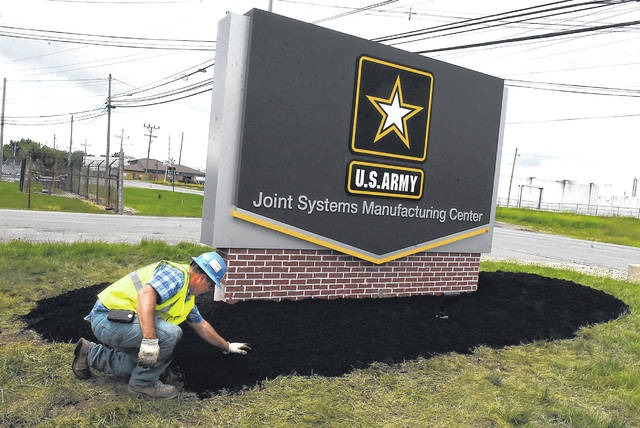 Andy Schwartz, an employee with Rudolph Libbe Inc., spreads mulch around the new U.S. Army Joint Systems Manufacturing Center sign set in place Thursday morning at the plant entrance on Buckeye Road in Shawnee Township.