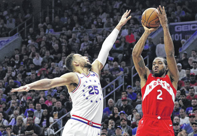 Toronto Raptors guard Kawhi Leonard shoots as the Philadelphia 76ers' Ben Simmons defends him during Toronto's 101-96 win Sunday. Leonard led the Raptors with 39 points.