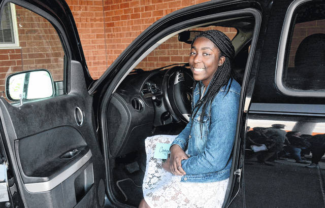 Ti'ara Spivey, of Lima Senior, poses with the new ride she won at the Lima Senior High School Honors Banquet. She was drawn from 25 students who maintained a 3.5 GPA, had no absences, no tardiness and no discipline referrals during the school year.