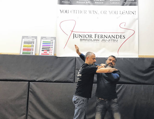 Jessy Austin (left) and Junior Fernandes demonstrate common Jui-Jitsu techniques. Fernandes was in town to train with students at Total Revolution Fitness, 914 MacKenzie Drive, Lima.