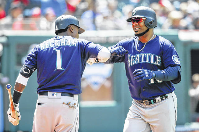 Edwin Encarnacion (10) of the Seattle Mariners celebrates with Tim Beckham (1) after hitting a two-run home run off Cleveland Indians relief pitcher Dan Otero during the fourth inning on Sunday in Cleveland.