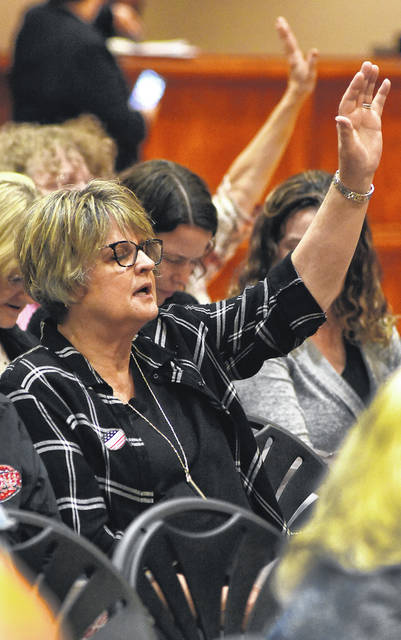 Kathy Kerr, of Lima, joins fellow business leaders, educators, musicians and city and county civic leaders, in Scriptures, songs and prayers and ask God's direction and protection during National Day of Prayer held at UNOH Event Center in Lima.