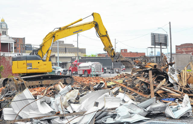 A backhoe cleans up the rubble from the former building that stood at the corner of Union Street and Central Avenue.