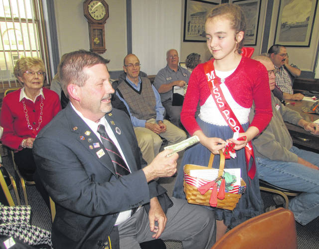 Dave Kersh, Ottawa American Legion Post 63 member, makes a donation for 10-year-old Ellianna Warren's poppy drive during Monday night's Ottawa council meeting.