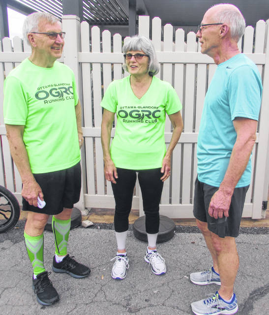 From left, Ottawa-Glandorf Run Club members Gene Hovest, his wife Barbara and member Mark Siefker talkl before Thursday's run.