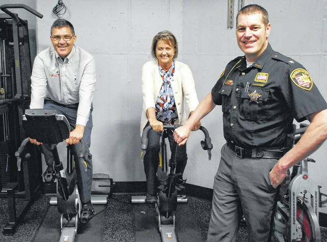 Paul Swartz, left, president of the Lima Rotary Club, and Past President Tracie Sanchez are pictured with Allen County Sheriff Matt Treglia in the newly-equipped fitness room at the sheriff's office. A Rotary Club donation of $6,000 made many of the improvements possible.