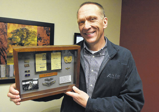 Tim Mosher shows memorabilia of Lima pilot Richard Brock, who was killed in a training mission during World War II.