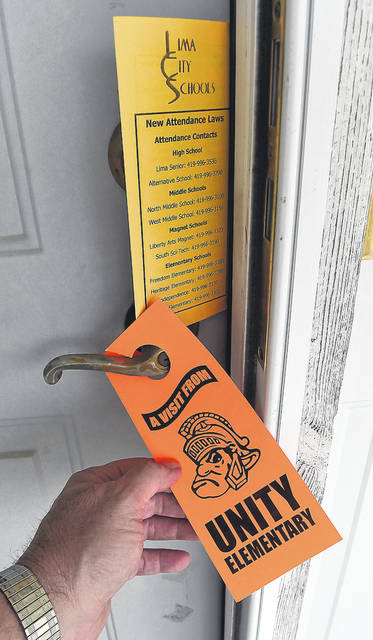 Lima schools places door hangers, made by its graphic arts department, on a door handle to remind parents of the rules for attendance. A recent state law increased the demands on local districts to communicate with parents about absenteeism.
