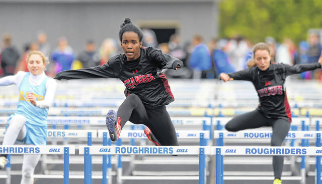 Shawnee's Karrington Green, center, competes in the 100 meter hurdles against Bath's Caitlin Bockrath, left, and teammate Chloe Conley during Friday night's WBL Championships at St. Marys.