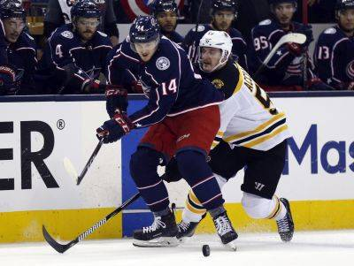 The Blue Jackets' Dean Kukan, left, and Boston's Noel Acciari chase the puck during Thursday night's Game 4 of a second-round playoff series in Columbus. (AP photo)