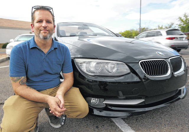 In this April 23, 2019, photo, Chris Williamson poses for a photo sitting next to his car in Phoenix. When Williamson was in the market for a new family car, a timely ad and conversations with a co-worker convinced him to try something out of the ordinary. He bought the BMW 3 Series convertible and covers the payments by renting it to strangers on a peer-to-peer car sharing app called Turo. It allows his family of seven to have a nicer car, essentially for free.