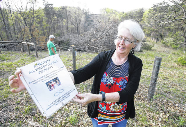 FILE - In this May 3, 2018, file photo, Becky Crabtree displays a flyer that she posted on a fence on the route of the proposed Mountain Valley pipeline on their property in Lindside, W.Va. A Virginia-based legal group is asking the U.S. Supreme Court to end what it says has become an abuse of eminent domain by companies that build natural-gas pipelines.