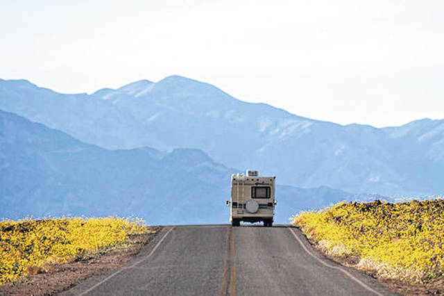 Wildflowers bloom as an RV travels along the road near Badwater Basin in Death Valley, Calif., in February 2016. Heading out on a road trip in a recreational vehicle allows travelers a unique opportunity to explore the nation while enjoying some comforts, too.