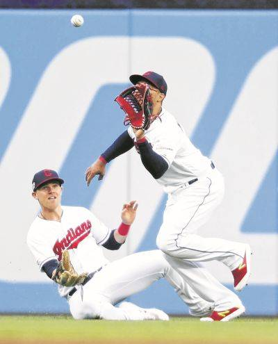 The Indians' Leonys Martin makes a running catch as Jake Bauers slides to avoid him during Tuesday night's game gainst the Chicago White Sox in in Cleveland.